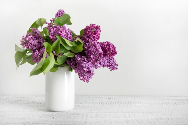 Bouquet of purple lilac flowers in white vase. space for text.