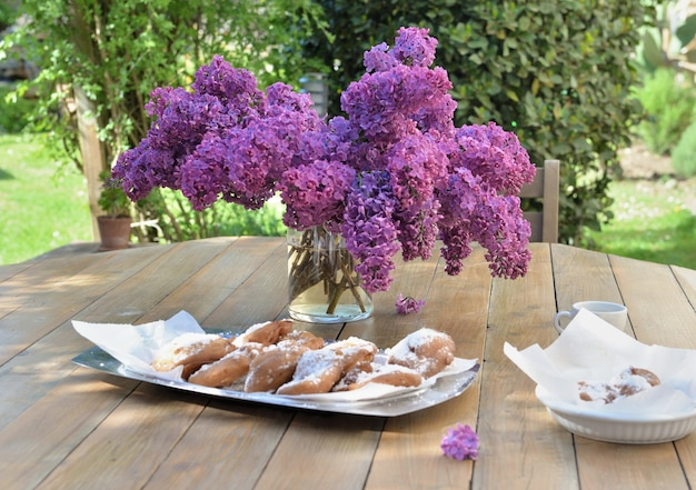 Bouquet of purple lilac on a wooden table with fresh donuts