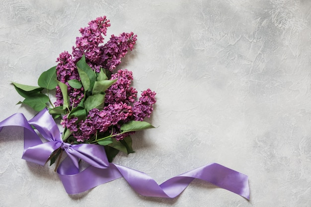 Bouquet of purple lilacs on light table in top view