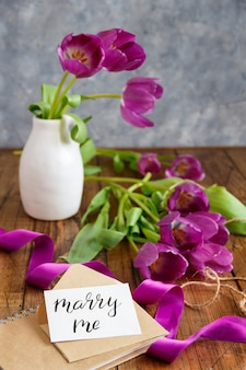 Bouquet of purple tulips and marry me card on wooden table close up