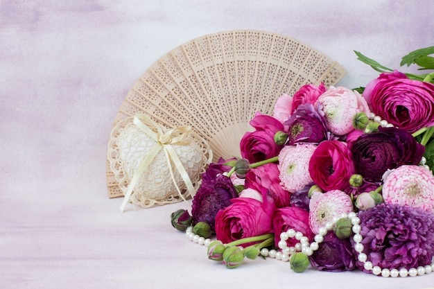 A bouquet of ranunculuses, a fan, a heart of lace and pearl beads
