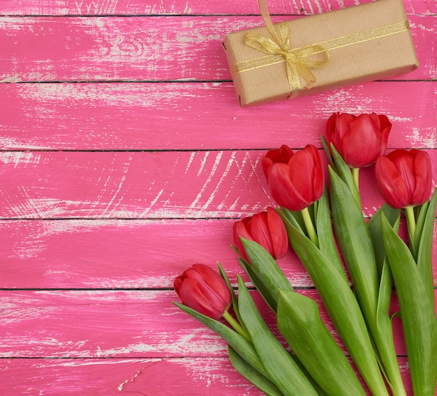 Bouquet of red blooming tulips with green leaves, wrapped gift in brown craft paper and tied with silk ribbon
