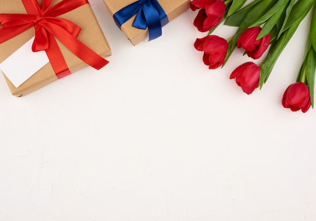Bouquet of red blooming tulips with green leaves, wrapped gift in brown craft paper on a white surface
