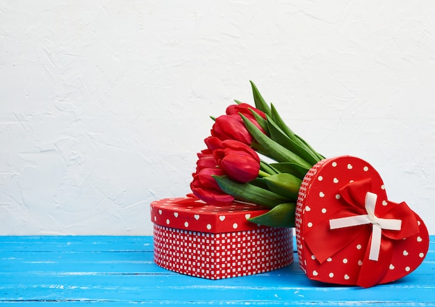 Bouquet of red blooming tulips with green leaves, wrapped gifts