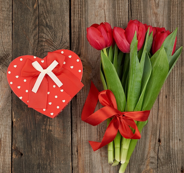Bouquet of red blooming tulips with green leaves