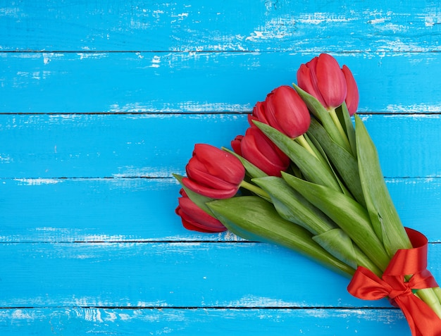 Bouquet of red blooming tulips with green stems and leaves tied with a red silk ribbon