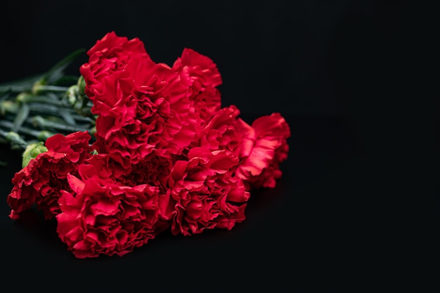 Bouquet of red carnations on a black . concept of mourning. copyspace.