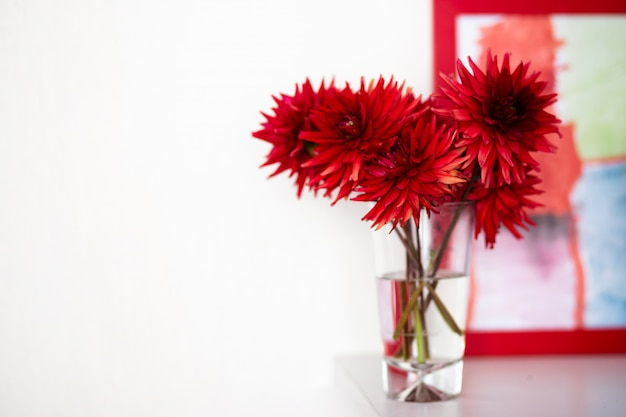 Bouquet of red dahlias in a glass vase in a light interior.