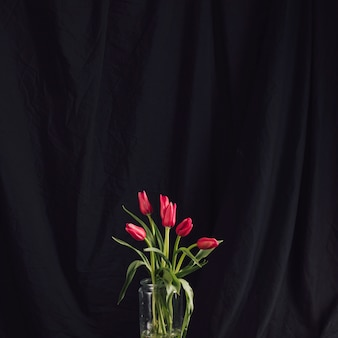 Bouquet of red flowers in vase with water