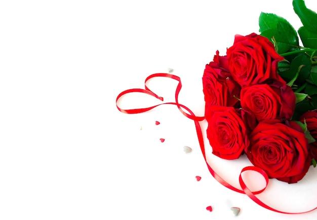 Букет красные свежие розы на белом фоне с красной лентой. плоская планировка. копирование пространства.