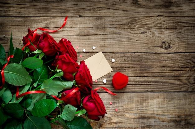 Букет красные свежие розы на красивой деревянной предпосылке с красной лентой, подарком, сердцем. плоская планировка. копирование пространства.