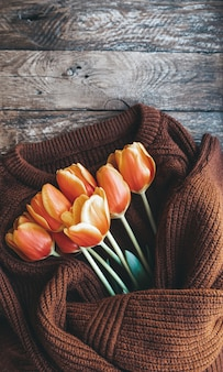 Bouquet of red and orange tulips on brown knit sweater