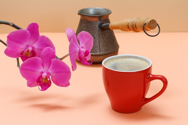 Bouquet of red orchid flowers, a cup of coffee and a copper coffeepot on the beige background.
