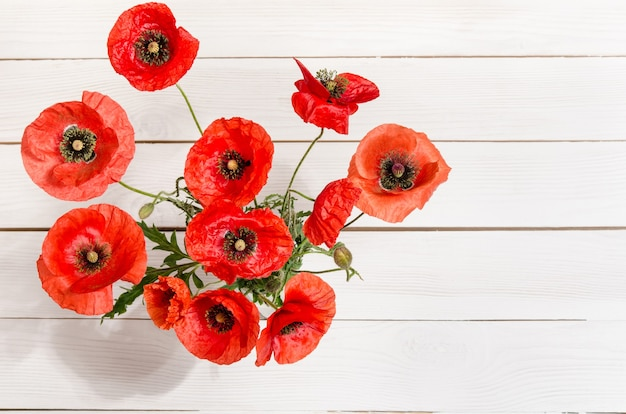 Bouquet of red poppies in glass vase on old white wooden table. top view