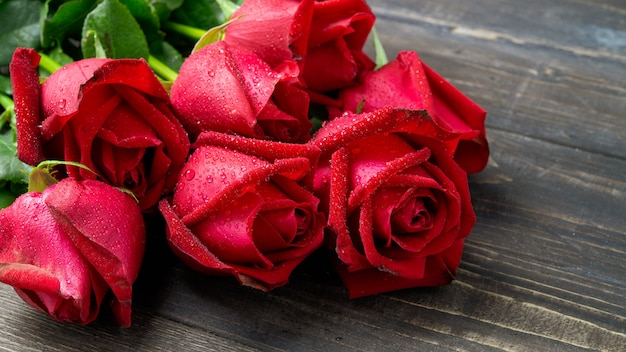 Bouquet of red rose flower on dark wooden table