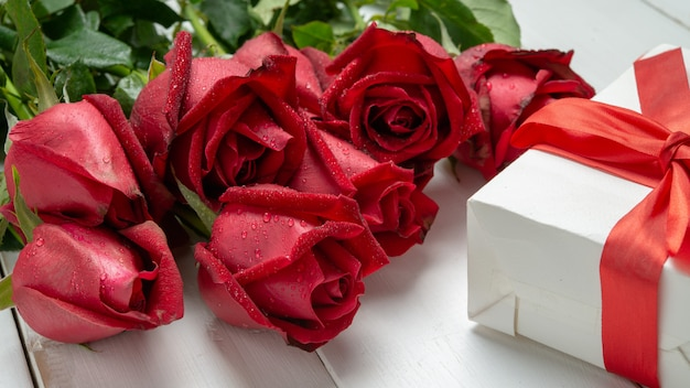 Bouquet of red rose flower and valentine day present box on white wooden table.