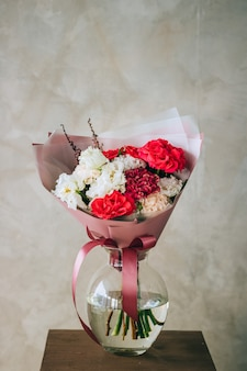 Bouquet of red roses, burgundy and white carnations, eustoma