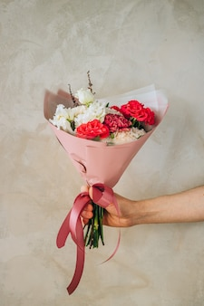 Bouquet of red roses, burgundy and white carnations, white eustomas