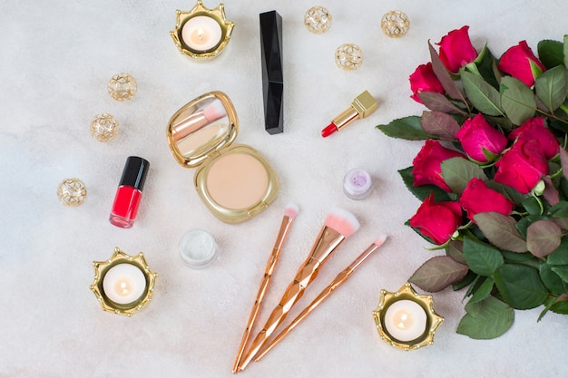 A bouquet of red roses, candles, decor and makeup items: brushes, lipstick, powder, mascara, eye shadow