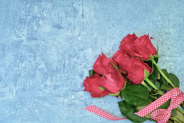 Bouquet of red roses decorated with ribbon on blue background. top view, copyspace.