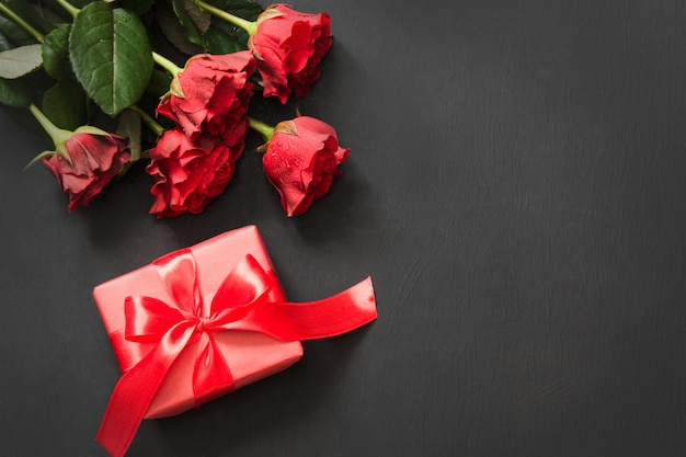 Bouquet of red roses and gift on black. valentine's card. copy space.