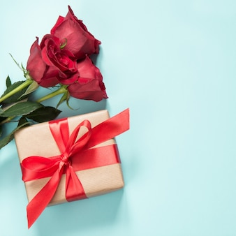 Bouquet of red roses and gift on blue. valentine's card. copy space.