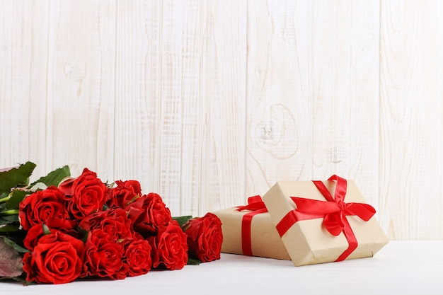 A bouquet of red roses, a gift on a white wooden table