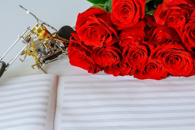 Bouquet of red roses and a motorcycle on a sheet for musical notes. congratulations to the musician. copy space.