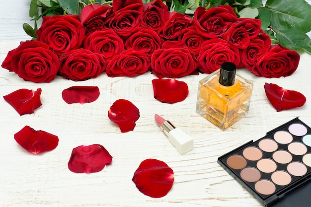 Bouquet of red roses, perfume, lipstick and eyeshadow palette on a white wooden table. top view