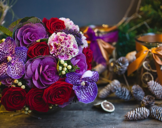 A bouquet of red roses, pink and purple flowers with leaves on the christmas table