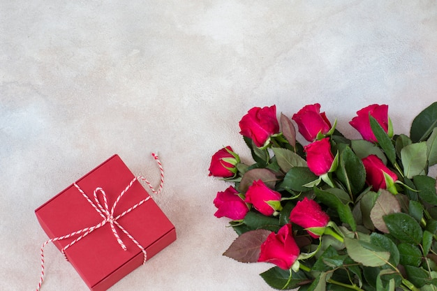 A bouquet of red roses and a red gift box