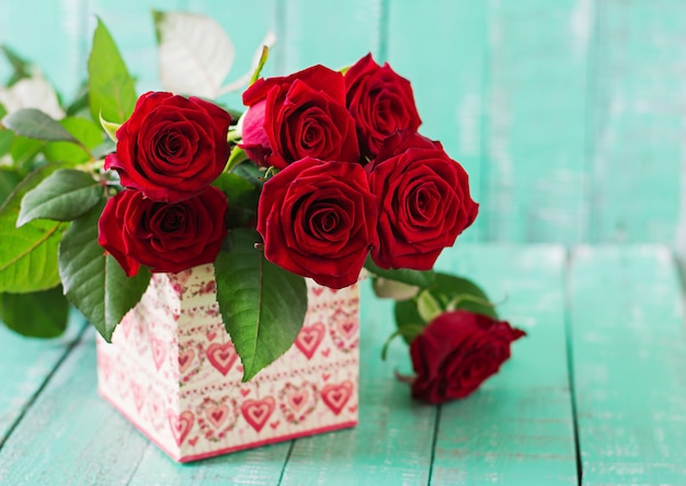 Bouquet of red roses on a wooden table.