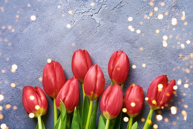 Bouquet of red tulips on a blue concrete wall. top view, copy space
