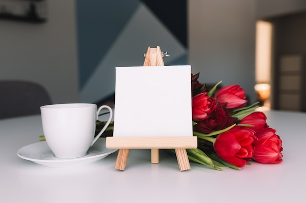Bouquet of red tulips and coffee cup. empty white frame. concept for greeting card