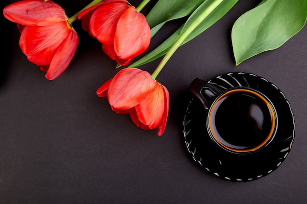Bouquet of red tulips and cup of coffee