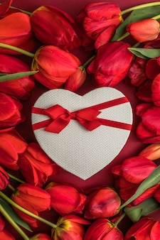 Bouquet of red  tulips and gift heart box, arrangement with a lot of copy space for text