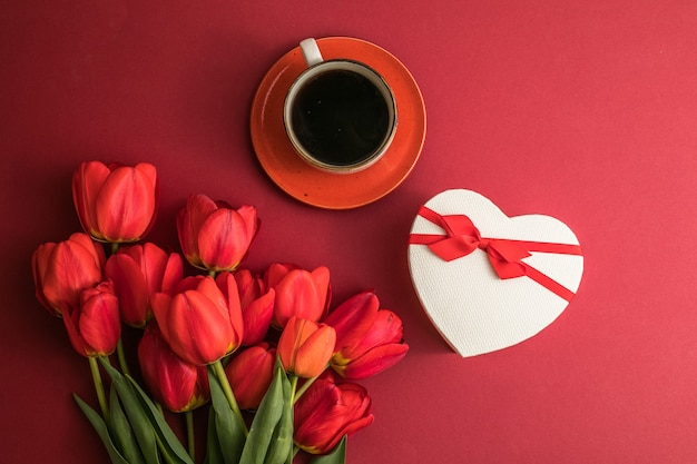 Bouquet of red  tulips and gift heart box, coffee cup arrangement with a lot of copy space for text