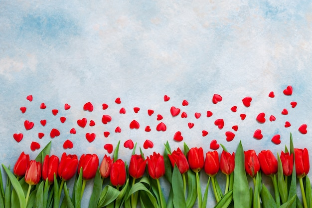 Bouquet  of red tulips and red heart figurines.