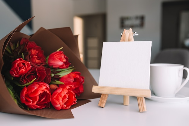 A bouquet of red tulips on the table and a white cup of coffee, empty white frame. concept for a greeting card.