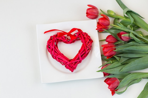 A bouquet of red tulips and a wicker red heart in a white plate