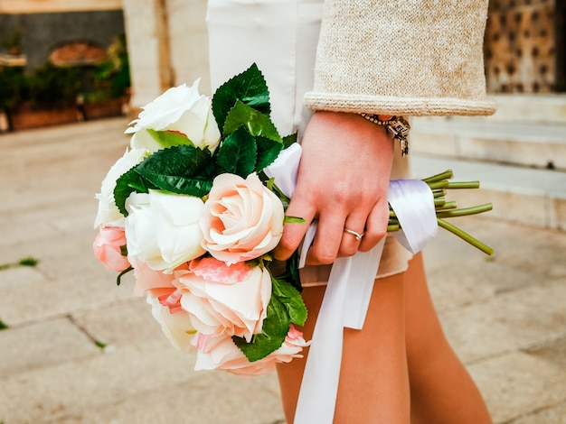 Bouquet of roses flowers in hands of modern hipster bride. modern minimalism wedding concept. urban background