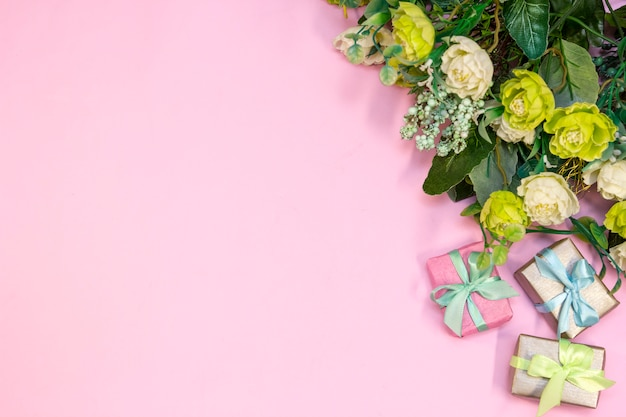 Bouquet of roses and gift boxes on pink background.