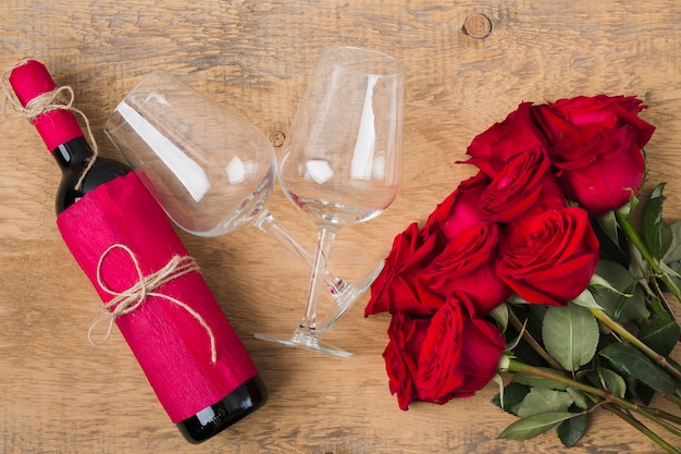 Bouquet of roses glasses and a bottle of wine