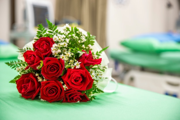A bouquet of roses on a hospital bed