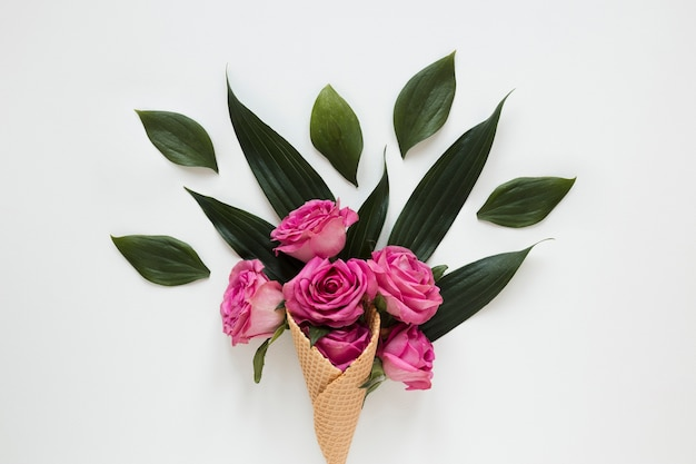Bouquet of roses and leaves wrapped in ice cream cone