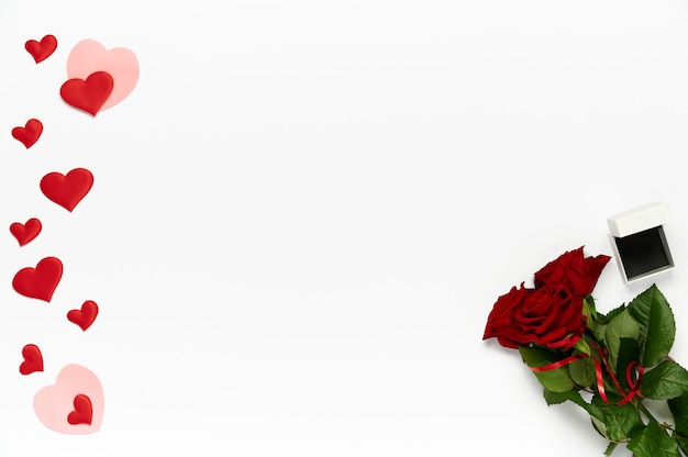 Bouquet of roses, many hearts and box for ring on white background. top view, flat lay