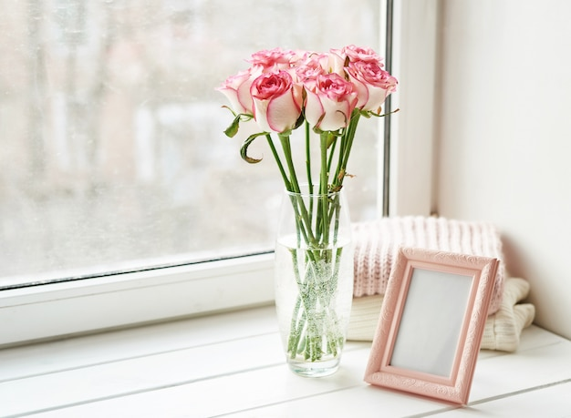Bouquet of roses and photo frame on window. valentine card. composition with fresh flowers. space for text. mother's day and march 8 card