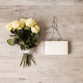 Bouquet of roses tied with white ribbon with clutch on wooden backdrop