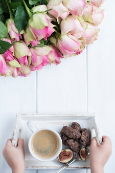 A bouquet of roses on a white background and a cup of coffee with chocolate in the hands of a girl