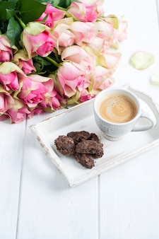Bouquet of roses on a white background and a cup of coffee with chocolate